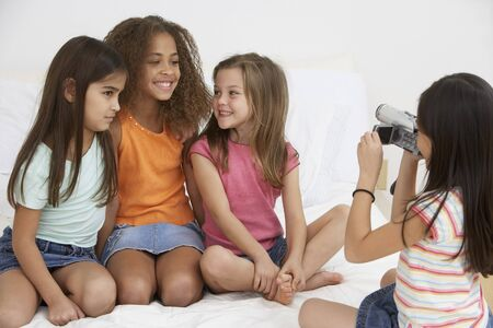 Group of young girls using video camera