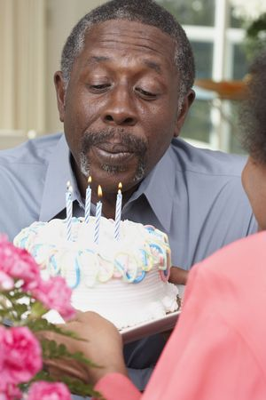 wooing: Senior African American man blowing out birthday candles