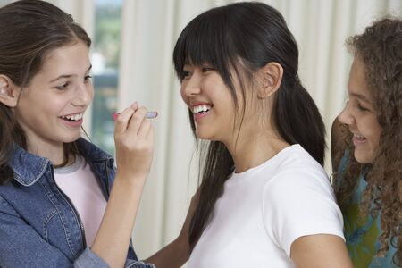 teenaged girls: Teenaged girls applying lipstick