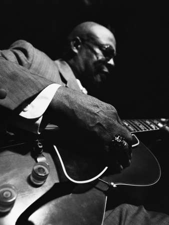 chinese american ethnicity: African American man playing guitar LANG_EVOIMAGES