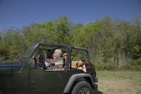 grampa: Hispanic family riding in jeep LANG_EVOIMAGES