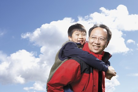 baby boomer: Asian father giving son piggyback ride outdoors