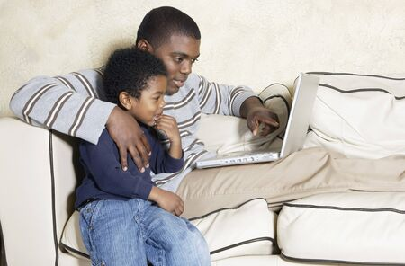 poppa: African American father and young son with laptop on sofa