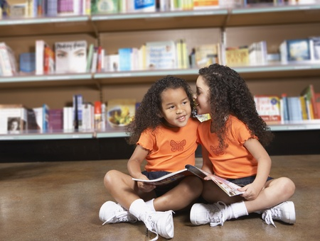 Two young sisters whispering in library LANG_EVOIMAGES