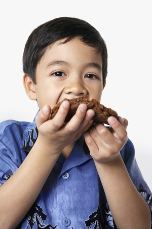 front raise: Studio shot of young boy eating cookie