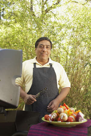 longshot: Hispanic man next to barbecue grill with kebabs