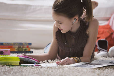 living wisdom: Young girl with headset doing homework on floor