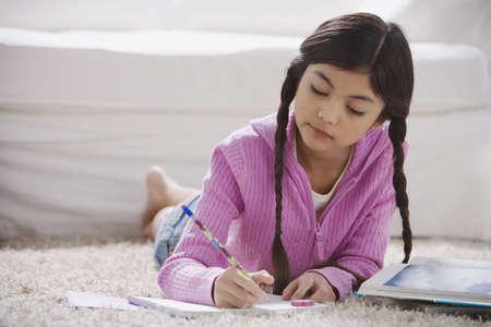 playing on divan: Young Hispanic girl doing homework on the floor