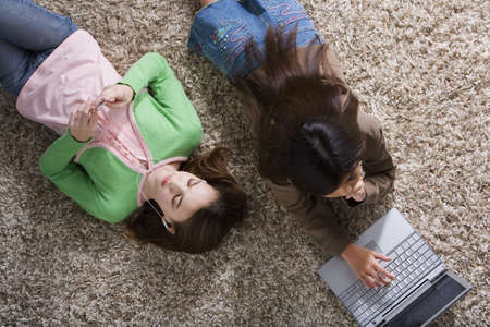 daydreamer: Two girls on the floor with MP3 player and laptop
