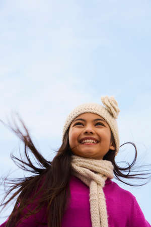 bathtowel: Young Hispanic girl wearing hat and scarf outdoors LANG_EVOIMAGES