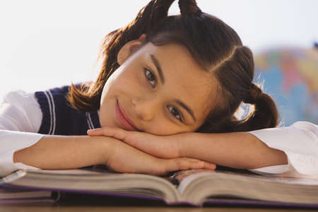 schoolroom: Young Hispanic girl at desk in classroom