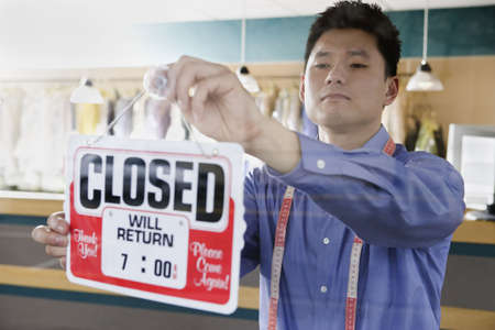 pacific islander ethnicity: Asian drycleaner putting up closed sign, Edmonds, Washington, United States LANG_EVOIMAGES