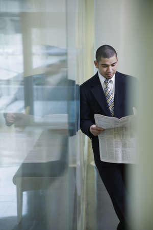 one mid adult man: Businessman with newspaper leaning on glass wall