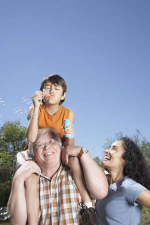 babyboomer: Hispanic grandparents and grandson blowing bubbles outdoors