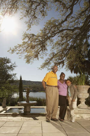 babyboomer: African American family hugging outdoors