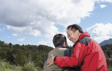 babyboomer: Asian father and son hugging outdoors