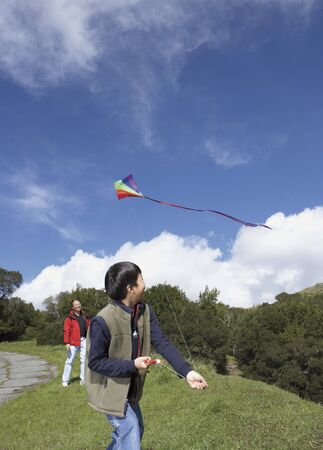 Asian father and son flying a kite