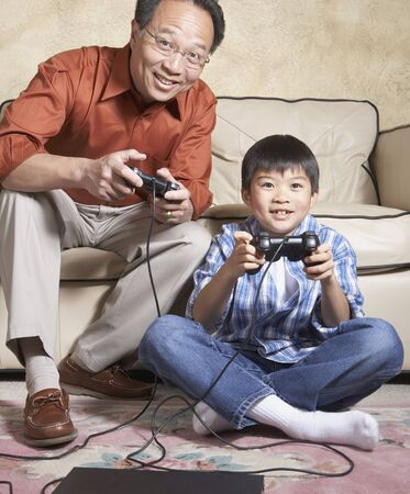 Asian father and son playing video games Banco de Imagens
