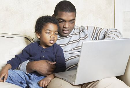 playing on divan: African American father and young son with laptop on sofa