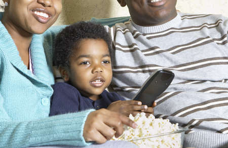 north western european descent: African American family watching television with popcorn