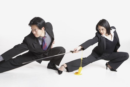 Studio shot of Asian businesspeople with swords Stock Photo