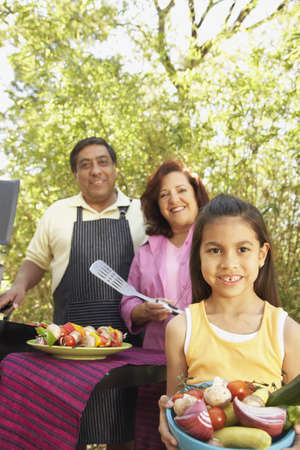bambino: Hispanic family using barbecue grill LANG_EVOIMAGES
