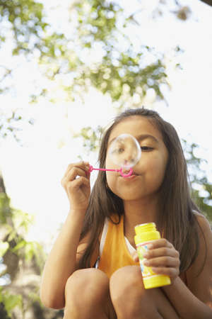 blowing bubbles: Hispanic girl blowing bubbles outdoors