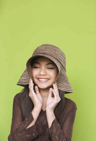 mischievious: Studio shot of young Hispanic girl with hat