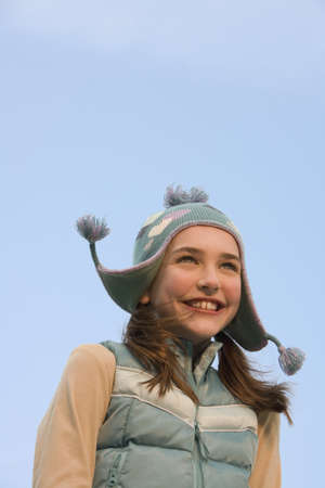 enclosing: Young girl wearing hat and vest outdoors