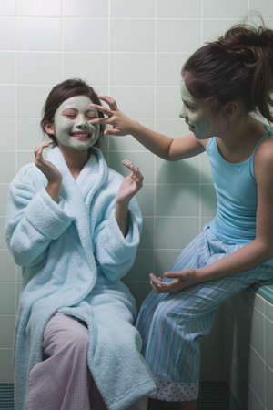 playing on divan: Two young girls applying facial masks in bathroom