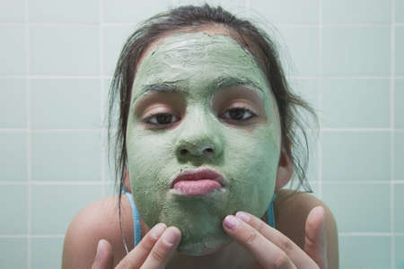 dressup: Close up of young Hispanic girl applying facial mask
