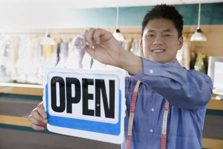 dressup: Asian drycleaner putting up open sign, Edmonds, Washington, United States