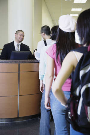 clothes organizer: Man sitting at reception desk with line of people