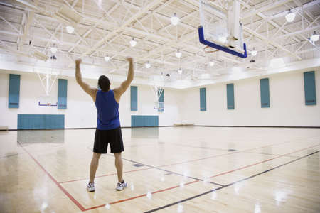 casualness: Man cheering on basketball court