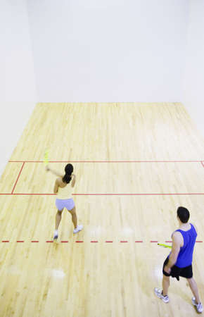 north western european descent: Man and woman playing Squash LANG_EVOIMAGES