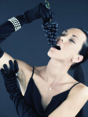 lower value: Woman with jewels eating bunch of grapes LANG_EVOIMAGES