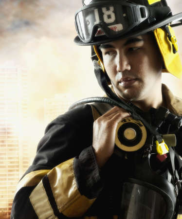 pacific islander ethnicity: Male fire fighter in front of burning building LANG_EVOIMAGES