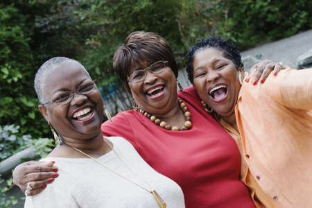 chic woman: Three middle-aged African women smiling and hugging LANG_EVOIMAGES
