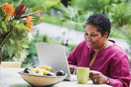 Mujer africana de mediana edad usando la computadora portátil al aire libre