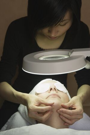 solicitous: Woman receiving facial at spa LANG_EVOIMAGES