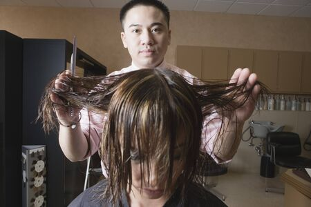 Asian male hairstylist cutting hair Stock Photo