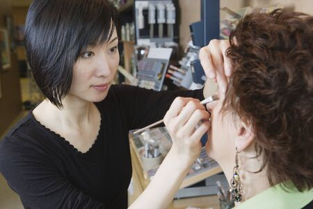 Asian female make up artist performing make over in salon