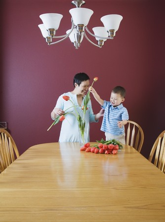 Mother and young son putting flowers in vase