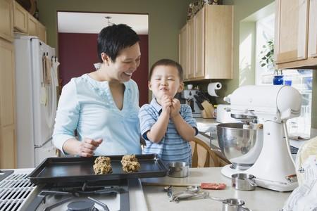 アジアの母と幼い息子のクッキーを作る