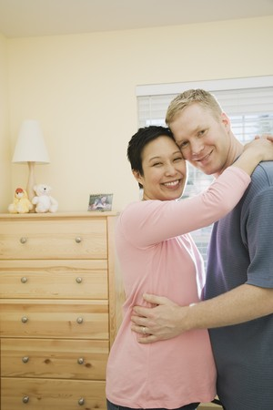 poppa: Pregnant couple hugging indoors