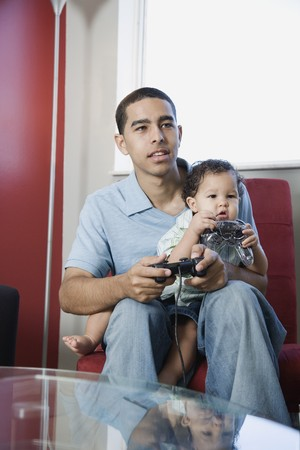 Young African father playing video games with baby on lap