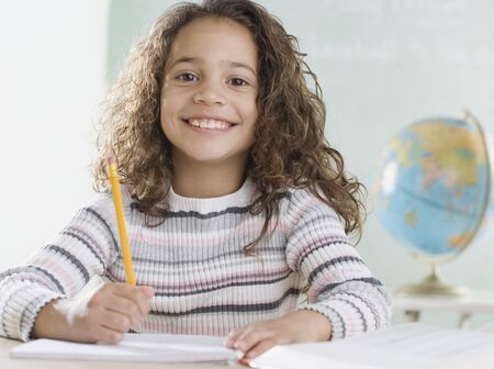 light hearted: Young girl in classroom smiling
