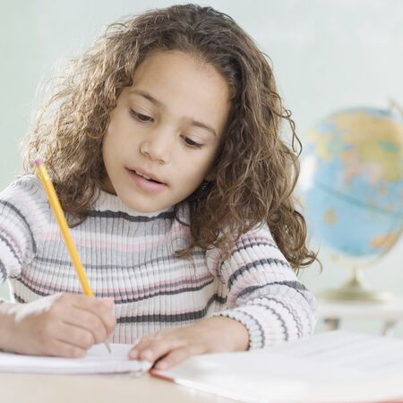 eagerness: Young girl working in classroom