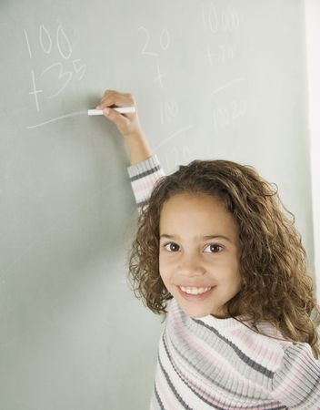cardboard only: Young girl writing on blackboard in classroom LANG_EVOIMAGES