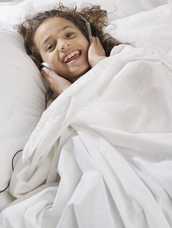 Young girl in bed listening to music Stock Photo
